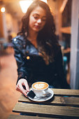 Young and beautiful woman sitting in a cafe and enjoying in her favorite coffee.