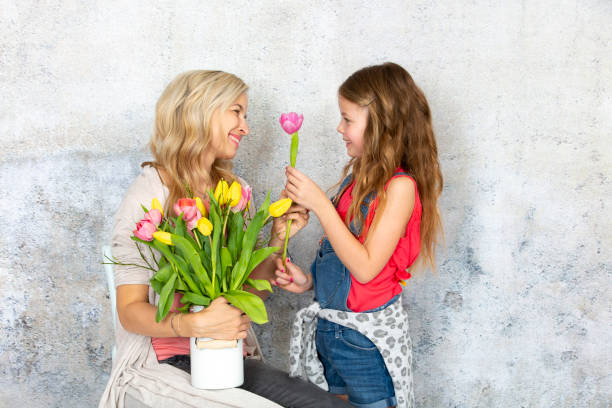 Young and blond and pretty mother gets a bouquet of colorful flowers from her daughter on Mothers Day stock photo