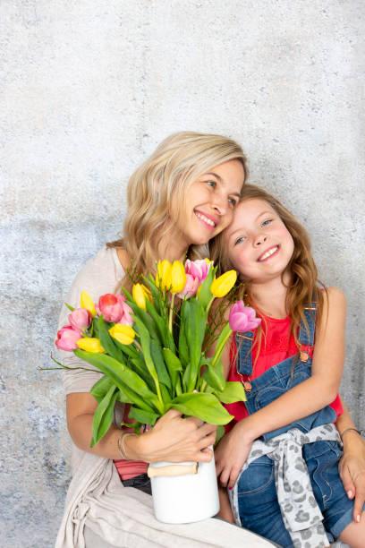 Jung, blond und hübsch Mutter bekommt einen bunten Blumenstrauß von ihrer Tochter am Muttertag – Foto
