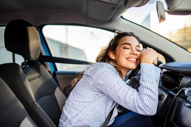 giovane e allegra donna che si gode una nuova auto che abbraccia il volante seduto all'interno - auto foto e immagini stock