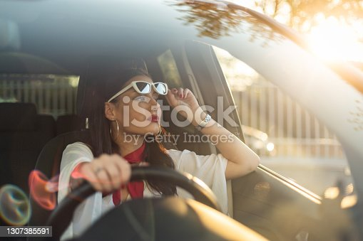 istock A young and cheerful woman enjoys a new car, sitting inside the car. 1307385591
