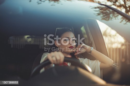 istock A young and cheerful woman enjoys a new car, sitting inside the car. 1307389053