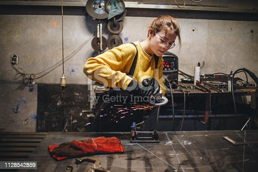 Young girl working at a metal workshop, grinding metal with grinder.
