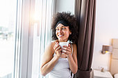 istock Young and cute lady sitting on the windowsill and looking out the window with cup of coffee in the morning. Young woman drinking coffee and wearing sleeping mask 1280139198