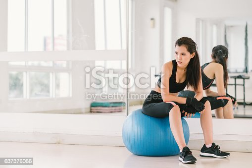 istock Young and determined Asian girl on fitness ball at gym 637376066