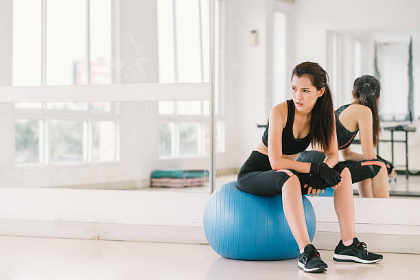 Young and determined Asian girl on fitness ball at gym stock photo