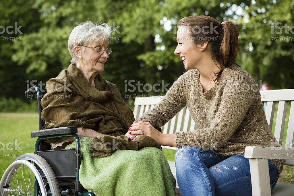 young and disabled senior woman have a talk in park stock photo