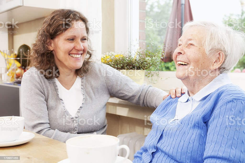 Young and elderly woman drink coffee and laugh stock photo