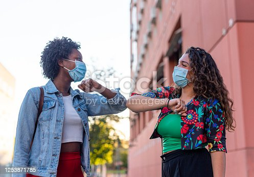 Young and friendly african girl and caucasian girl keeping social distance, greeting each other by bumping elbows instead of hugs, kisses or handshaking, wearing mask for prevent corona virus infection