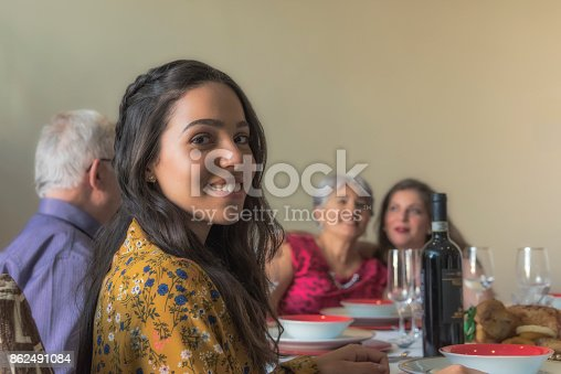 1035768506 istock photo Young and friendly woman celebrating Christmas with family 862491084