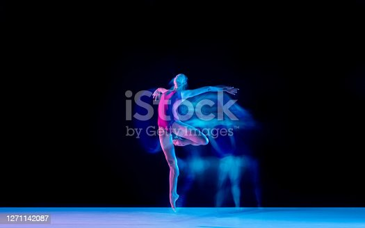 Smoke. Young and graceful ballet dancer on black studio background in neon mixed light. Art, motion, action, flexibility, inspiration concept. Flexible caucasian ballet dancer, weightless jumps.