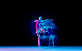 istock Young and graceful ballet dancer isolated on black studio background in neon mixed light 1271142087