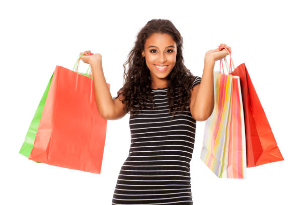 Jeune et heureuse femme peau brune avec des sacs à provisions sur fond blanc - Photo