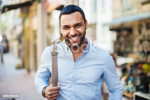 Cheerful young man walking on the street.