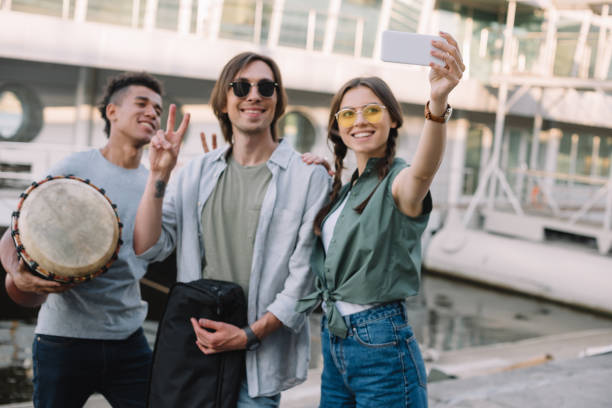 young and happy street musicians with instruments taking selfie in city - concert selfie stock photos and pictures