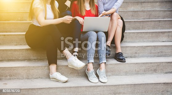 istock young and happy urban people sitting on steps with gadgets 825576720