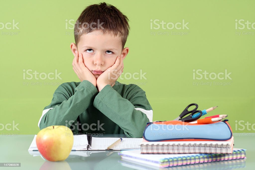 A young and irritated boy with lots of homework royalty-free stock photo