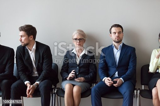 Group of serious young and middle aged candidates professionals business people sitting in chairs in queue waiting job interview, for one position at company. Human resources, hr, recruitment concept