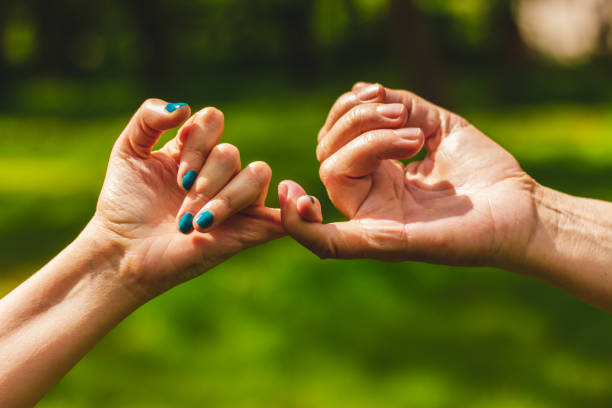 Young and mature hand making pinkie promise sign stock photo