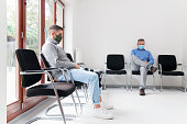 istock Young and mature man with face masks sitting in a waiting room of a hospital or office 1278549866