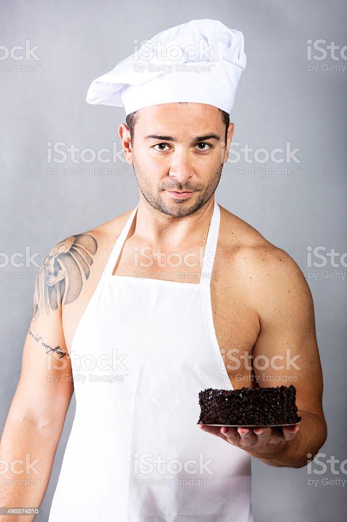 Jovem e muscled chef segurando bolo - foto de acervo