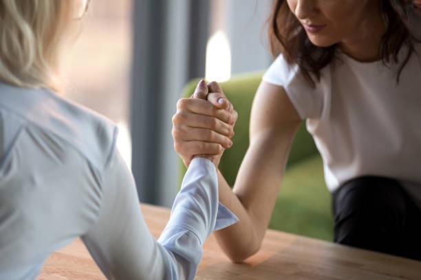 jung und alt geschäftsfrauen konkurrieren arm wrestling kampf für führung - armdrücken stock-fotos und bilder