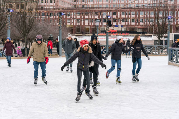 Young and old people skating at a public ice skating rink outdoors. stock photo