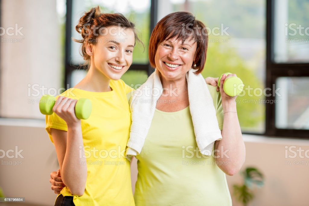 Young and older woman exercising indoors - foto stock