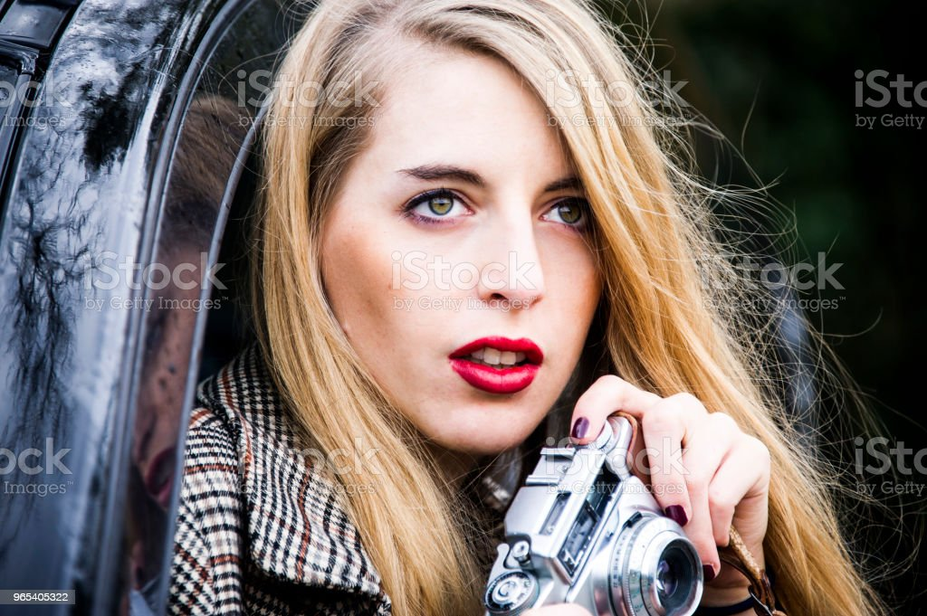 Young and pretty blonde woman is taking photographs from her car. royalty-free stock photo