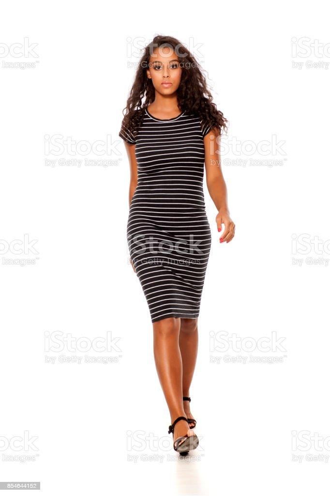 jeune et jolie noir peau femme marchant sur fond blanc - Photo