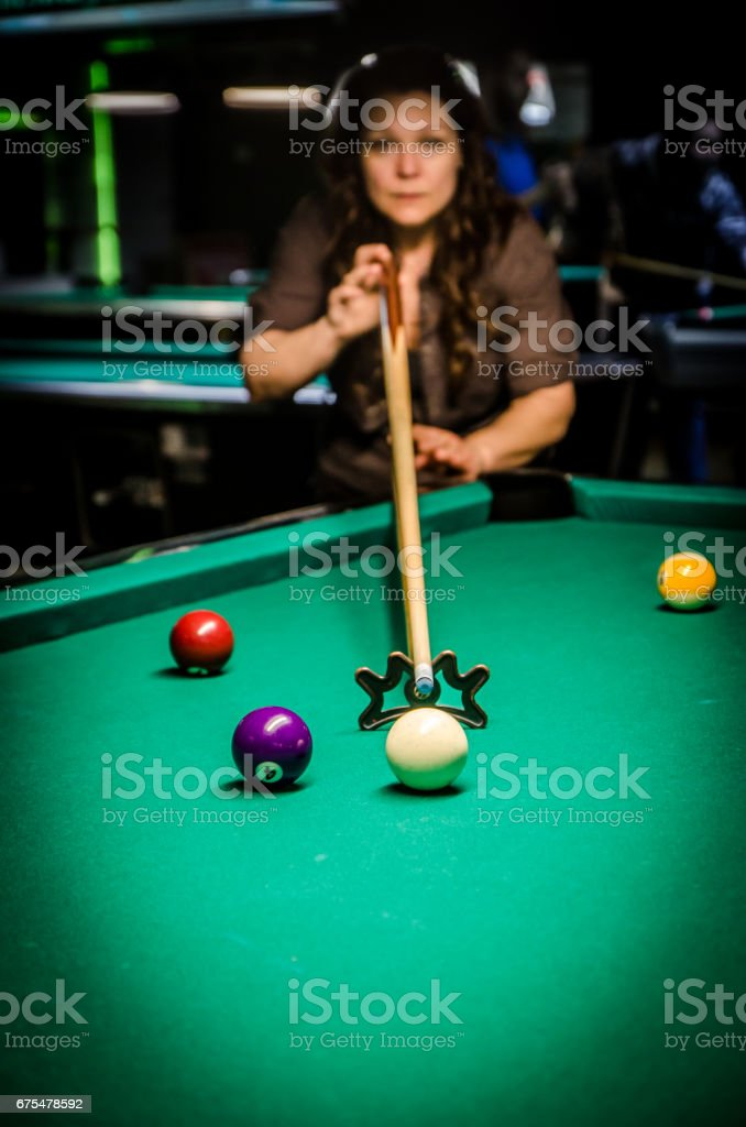 Young and pretty woman using bridge stick to hit cue ball during pool...
