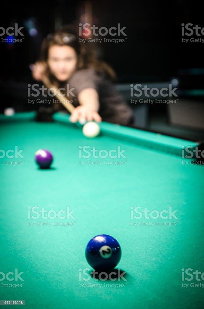 Jeune et jolie femme à l'aide de queue pour frapper la boule blanche au cours du jeu de billard photo libre de droits