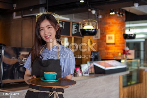 istock Young and proud Asian female barista serving coffee to customer 1152604282