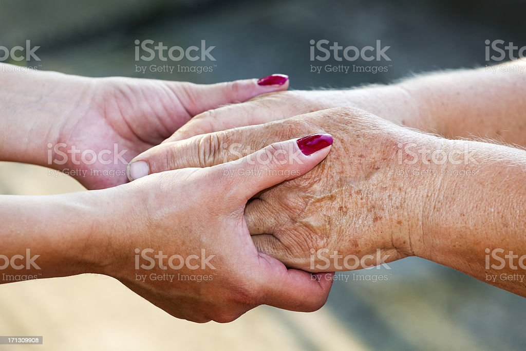 Young and senior women holding hands royalty-free stock photo