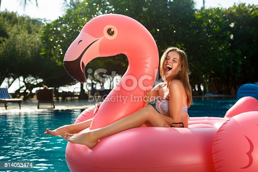 istock Young and sexy girl having fun and laughing on an inflatable giant pink flamingo pool float mattress in a bikini. Attractive tanned woman lies in the sun on vacation 814053474