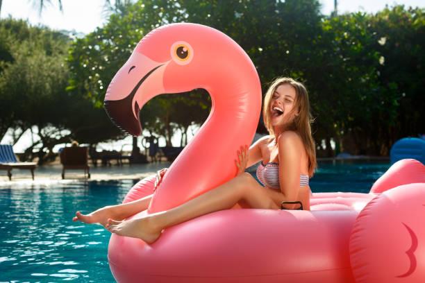 Jeune et sexy girl s'amuser et de rire sur un matelas de flotteur gonflable géant rose flamingo piscine en bikini. Jolie femme bronzée se trouve au soleil en vacances - Photo