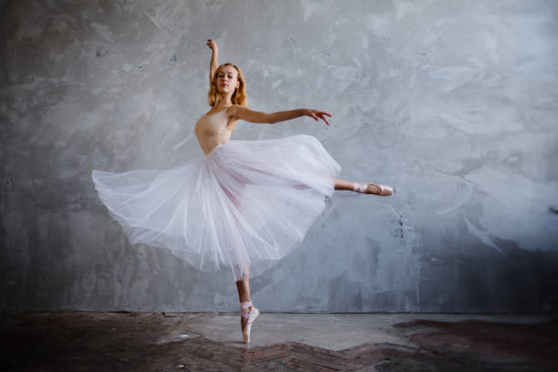 Young and slim ballet dancer is posing in a stylish studio with big windows stock photo