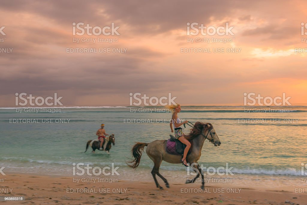 Young and slim european woman riding a horse on a tropical beach in the sunset - Royalty-free Activity Stock Photo