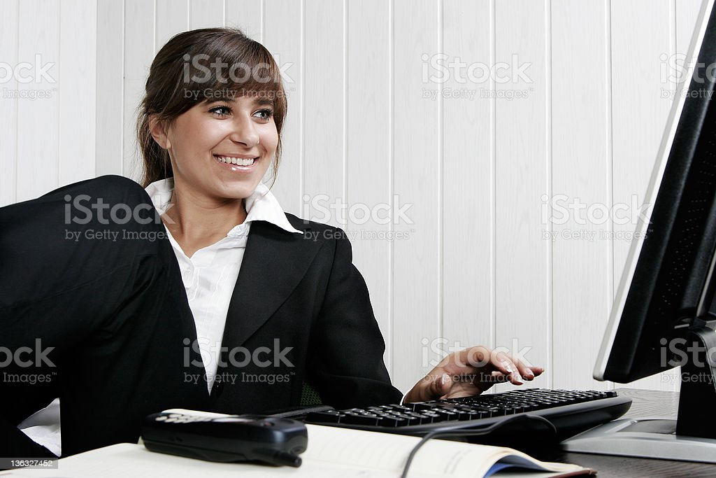 Young and smiling woman works on a computer royalty-free stock photo