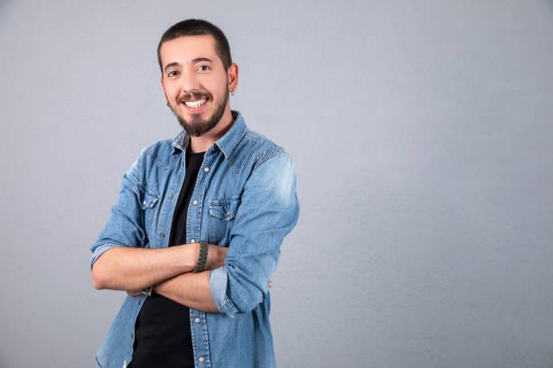 Jung und sportlich gekleidete Mann lächeln über graue Hintergründe – Foto