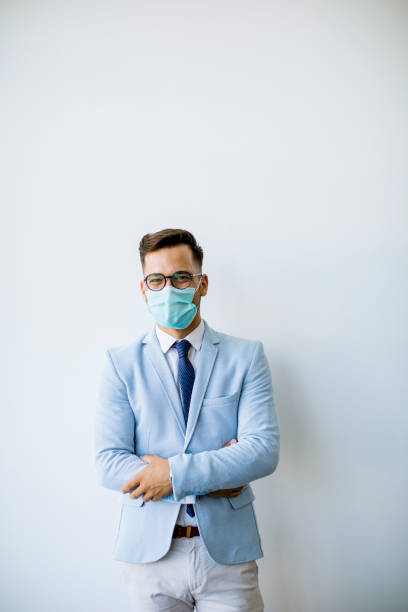 Young and stylish business man with face mask stands by the wall in the office stock photo