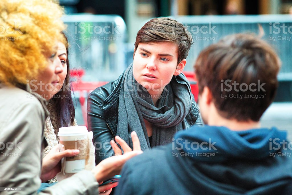 Young androgynous woman listens to friend with interest stock photo