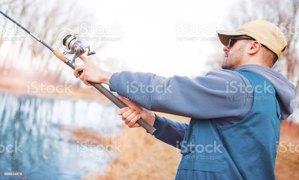 Young angler enjoys in fishing on the river. Sport, recreation, lifestyle stock photo