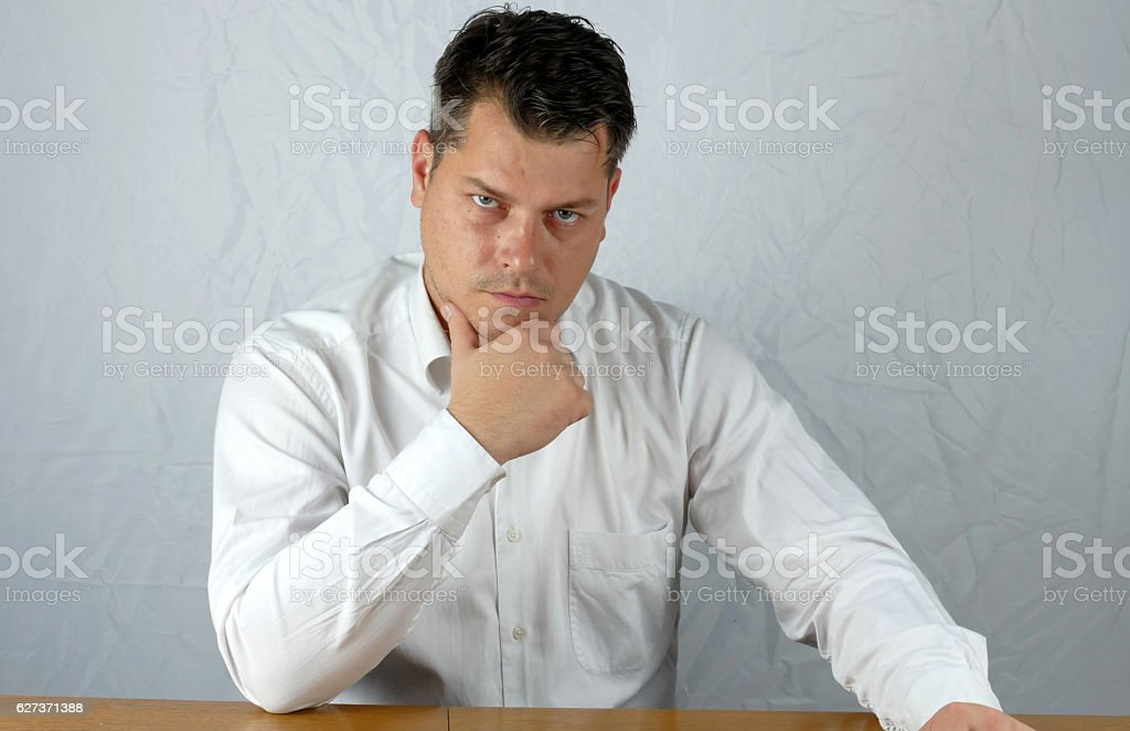 Young angry business man watching stock photo