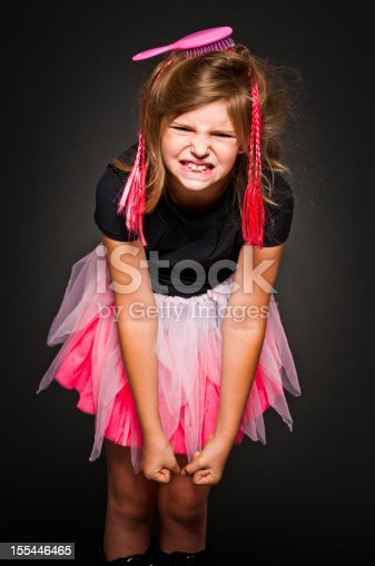 9 years old girl which looks like a doll is angry, she has clenched teeth and fists. Hair brush in hair, artificial braids, Black background, studio shot.