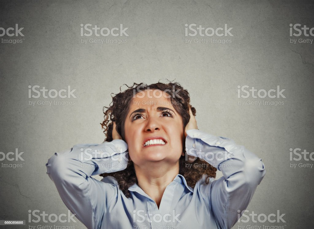 young angry unhappy stressed woman covering her ears stock photo