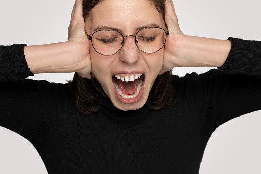487960859 istock photo Young Angry woman shouting overt isolated gray background 1214933880
