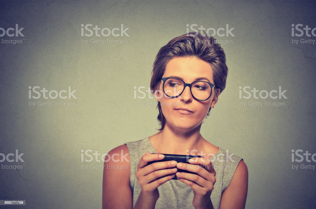young angry woman with glasses unhappy, annoyed by something on cell phone foto stock royalty-free