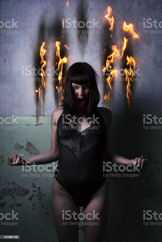 Young angry woman with hot flames on the background wall royalty-free stock photo