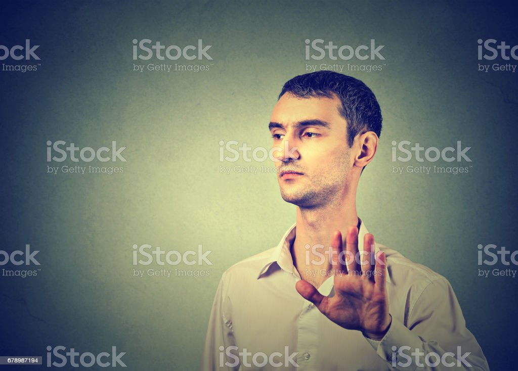 Young annoyed angry man with bad attitude giving talk to hand gesture with palm outward stock photo